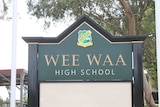 A green sign at the front of Wee Waa High School in north west NSW, with trees and an awning in the background.