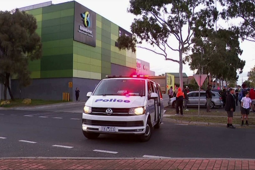 A police van is parked outside a shopping centre with a number of people nearby including children sitting on a curb.