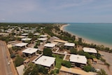 A drone photo of the town of Nhulunbuy. Blue water is in the background.