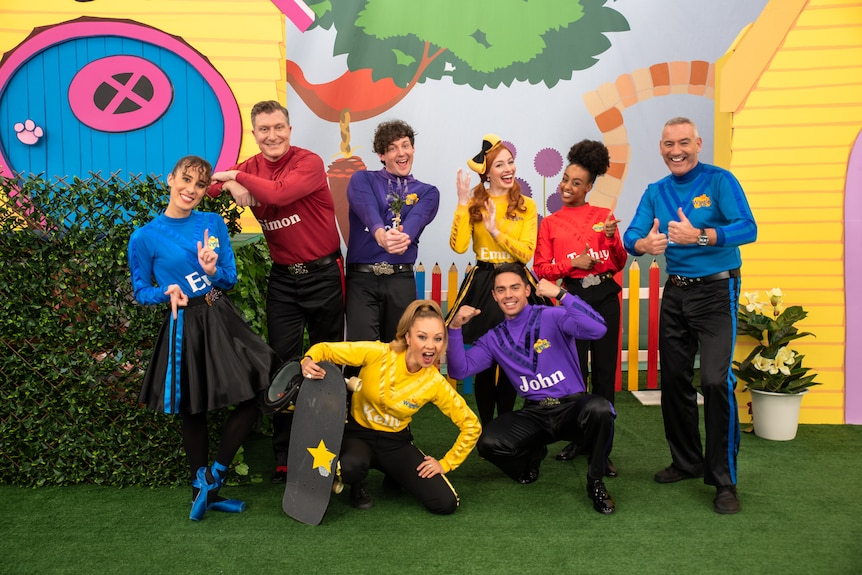 Eight Wiggles dressed in red, blue, purple and yellow skivvies pose together.