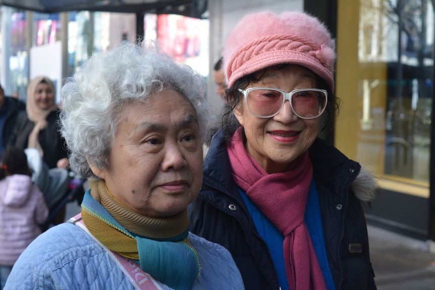Two elderly women of Asian descent look are pictured close-up while one wears a pink furry hat.