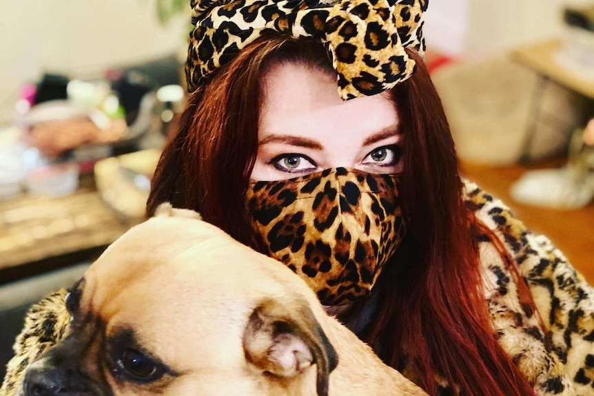 A woman holds her dog wearing a leopard print outfit and mask.