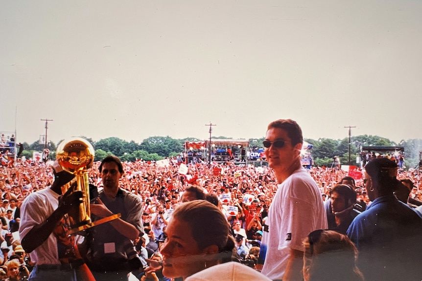 View from the stage looking over a large crowd of Chicago Bulls fan. Luc Longley looks back at camera