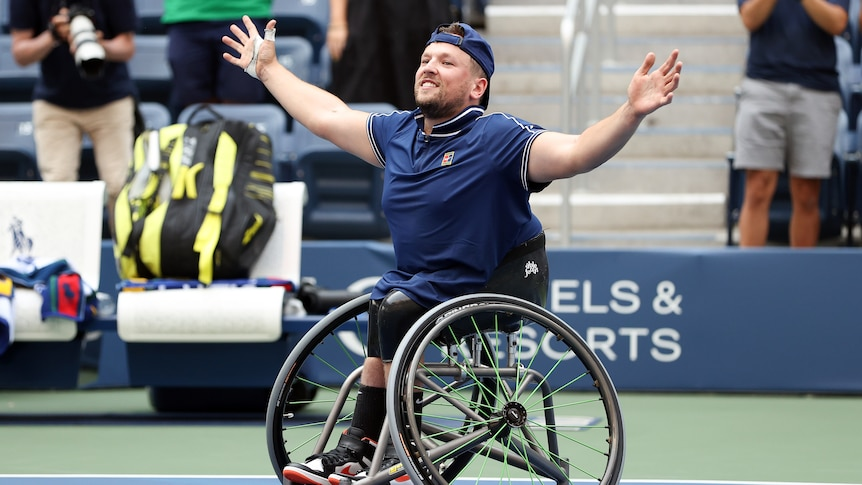 A smiling Dylan Alcott holds his arms out wide on court after the final point of his US Open quad singles final.