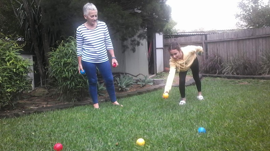 Wendy Lawson and her grand-daughter Gabby playing boule in the backyard