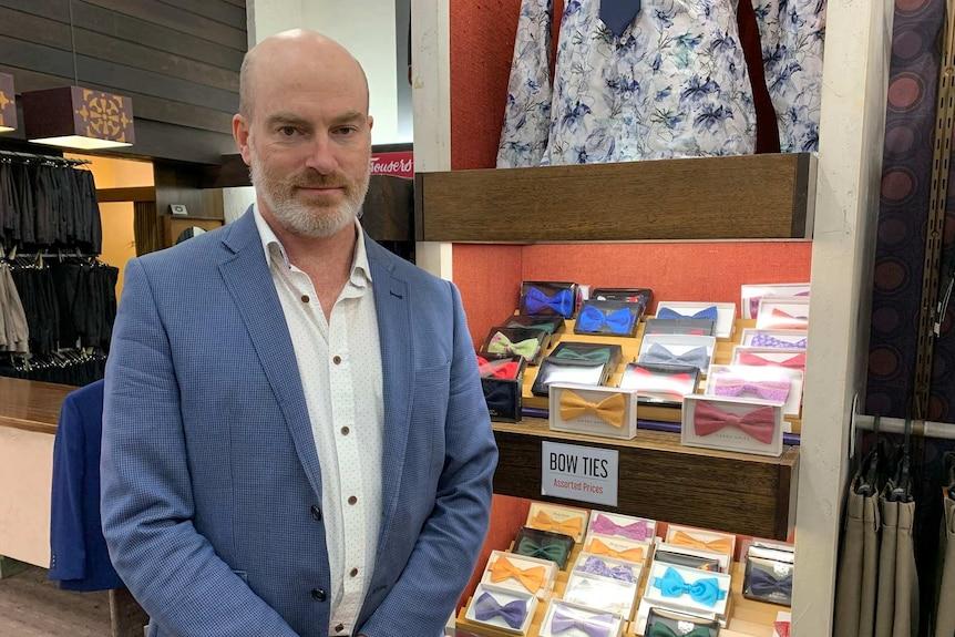 Un homme se tient devant un stand de cravates dans un magasin de vêtements pour hommes.