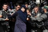 Israeli security forces arrest a Palestinian woman during clashes at al-Aqsa mosque