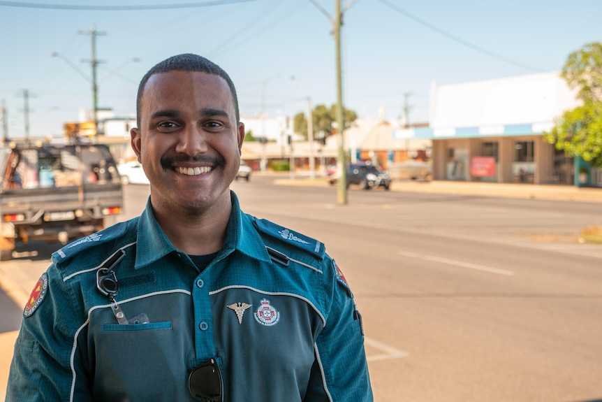 A young Indigenous man in a paramedic uniform stands outside, smiling.