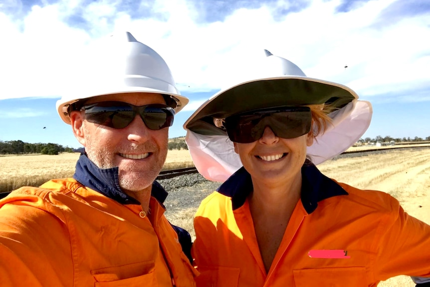 A man and a woman in high-vis, helmets and dark sunglasses smile for a selfie, a paddock behind them.