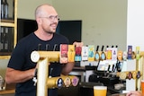 A tall man standing behind the beer taps at a bar smiling at customers.