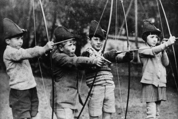 A group of young children with bow and arrows, wearing Robin Hood hats.