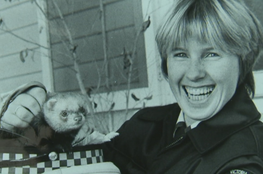 A black and white photo of a female police officer, holding a ferret in her hat.