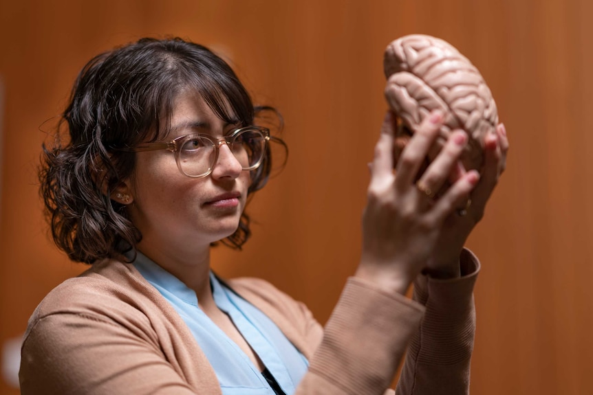 A woman holds a model of a brain up to the light.