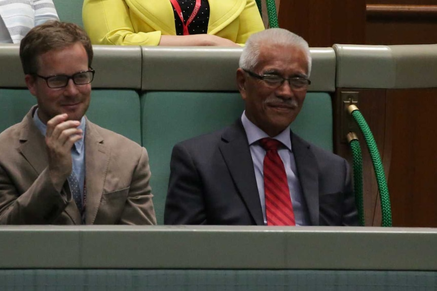 Mr Tong sits in the front row of the gallery, smiling.