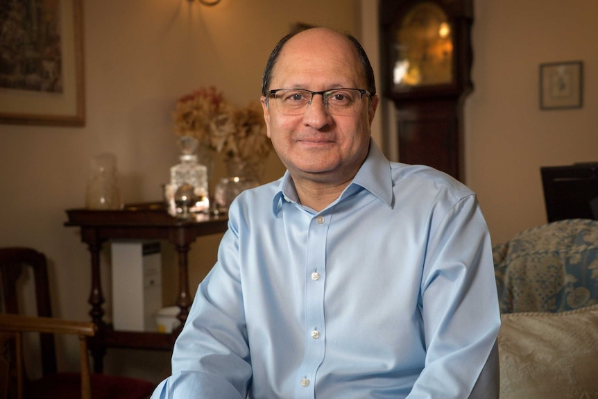A balding man wearing glasses and a blue shirt sits on a couch.
