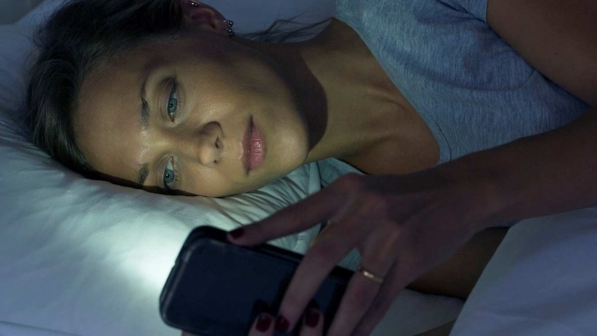 Woman lying on her side in bed using mobile phone with light from screen reflected on her face