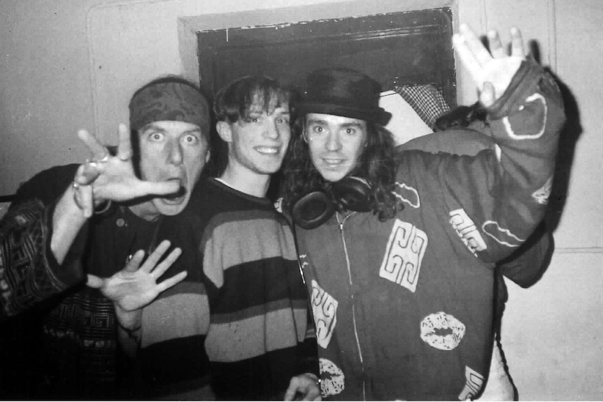 Three young men act up for the camera, black and white photo, man on right wears top hat and has large headphones around neck.