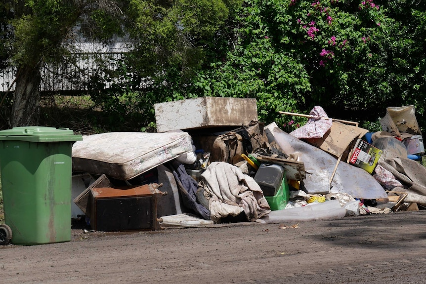 A pile of dirty and muddy furniture including mattresses and couches and boxes