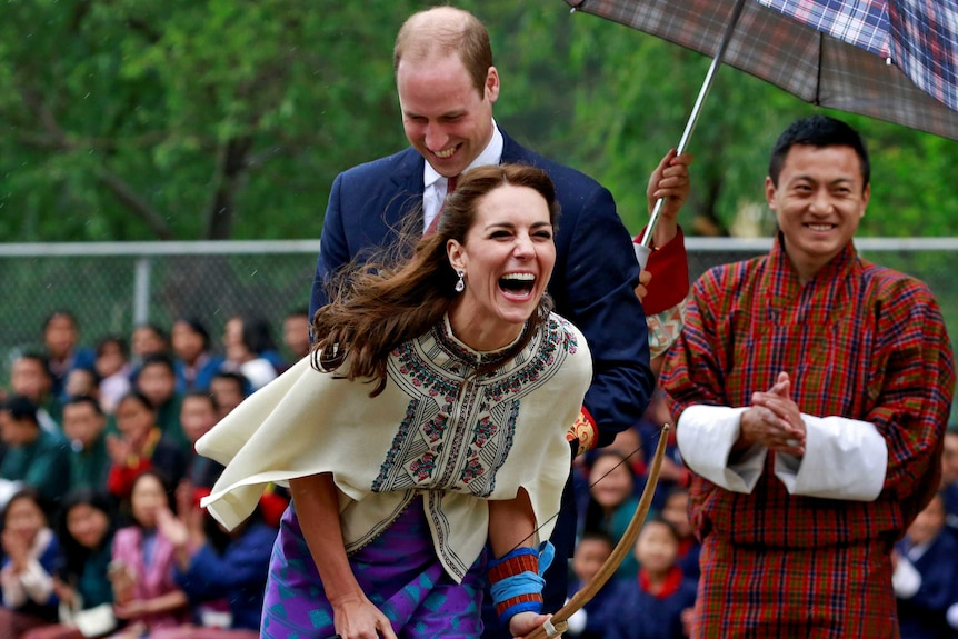 Catherine laughs holding a bow and arrow at an archery ground.