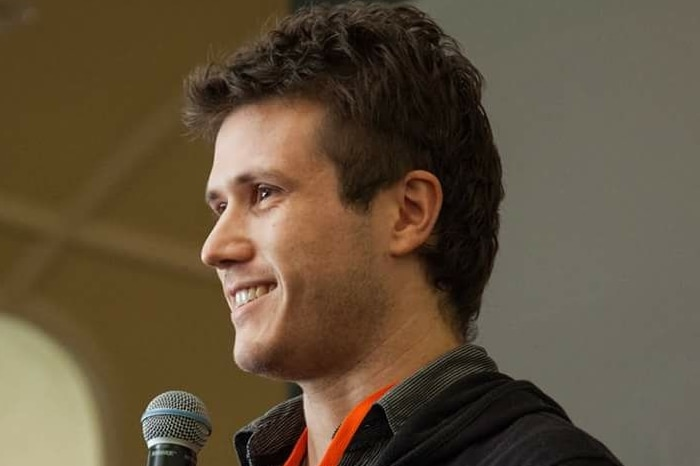 Man holding microphone looking left