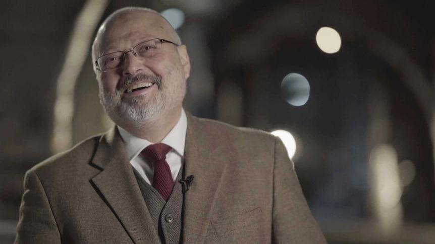 Jamal Khashoggi in a brown suit speaking to camera.