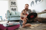 A man and his son look at a record on the floor of their living room