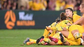 The Matildas pile on to celebrate a goal.