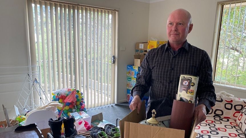 Man with a box of items as he prepares to move out of his unit