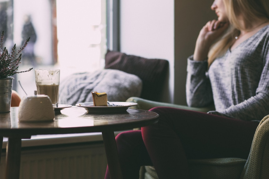 Woman in front of cake and coffee looking pensively out the window