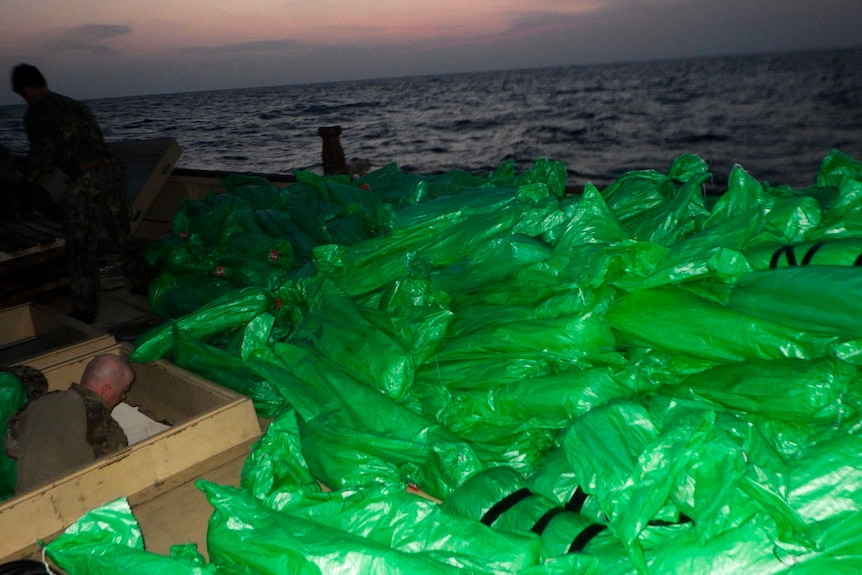 green bags rapped in black tape are bundled together on a boat at sea at night