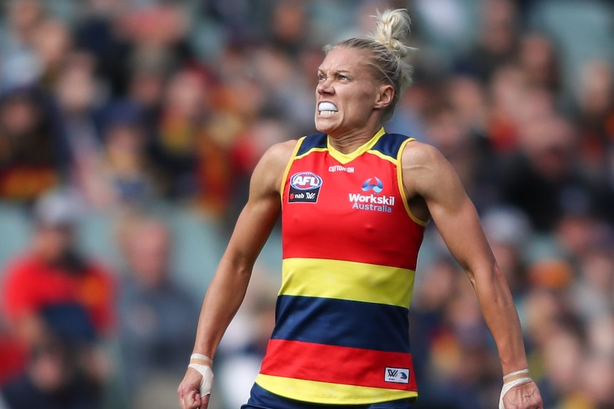 An Adelaide Crows AFLW player celebrates kicking a goal against Melbourne.