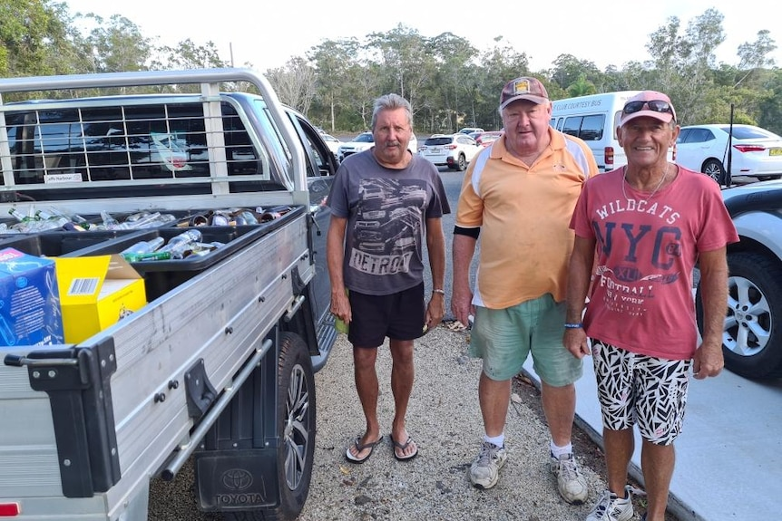 Three older men standing next to a ute filled with bottles to recycle.