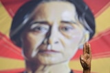 A person shows the three-fingers salute in front of a placard with the image of Aung San Suu Kyi.