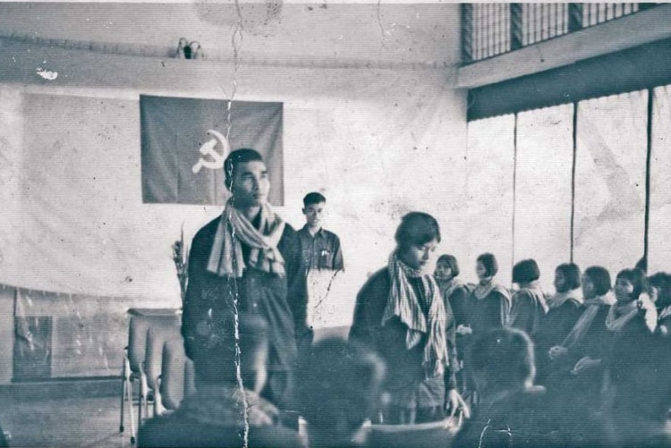 A black and white photo showing a man standing next to a woman with a hammer and sickle flag in the background.