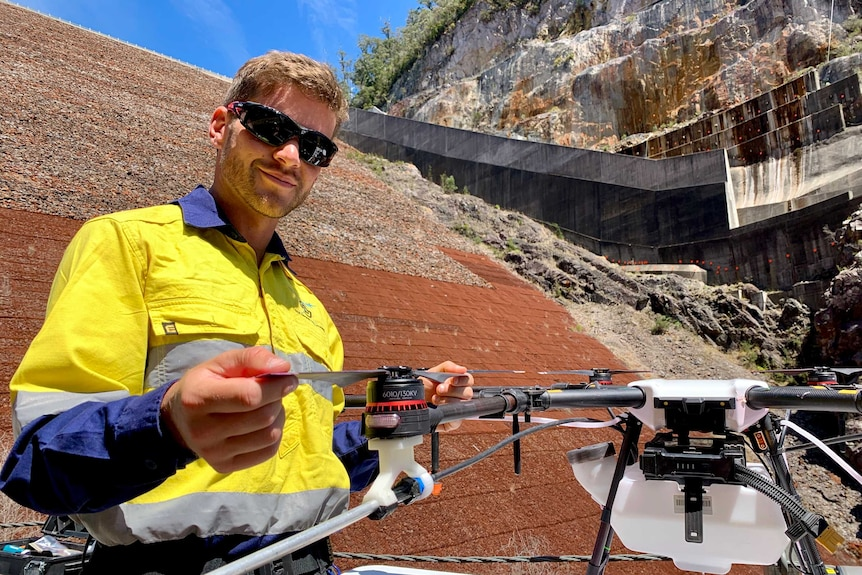 A man is wearing work gear and setting up his drone to fly and spray weeds in a dam.