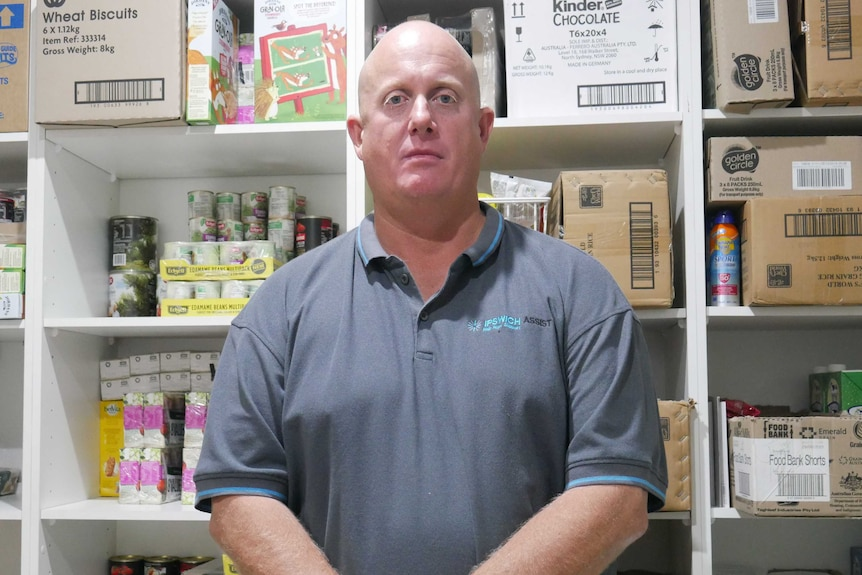 Man stands in front of shelves packed with food