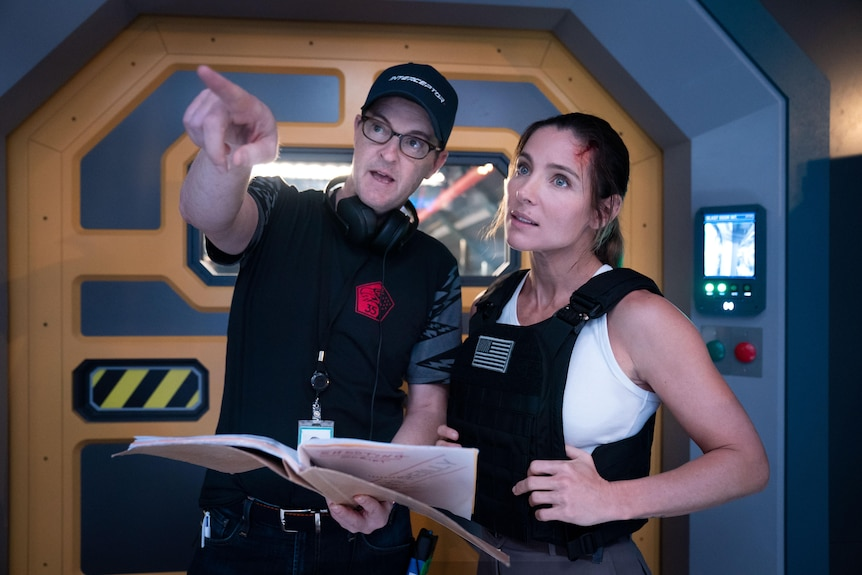 A director points to the distance standing next to an actress in costume