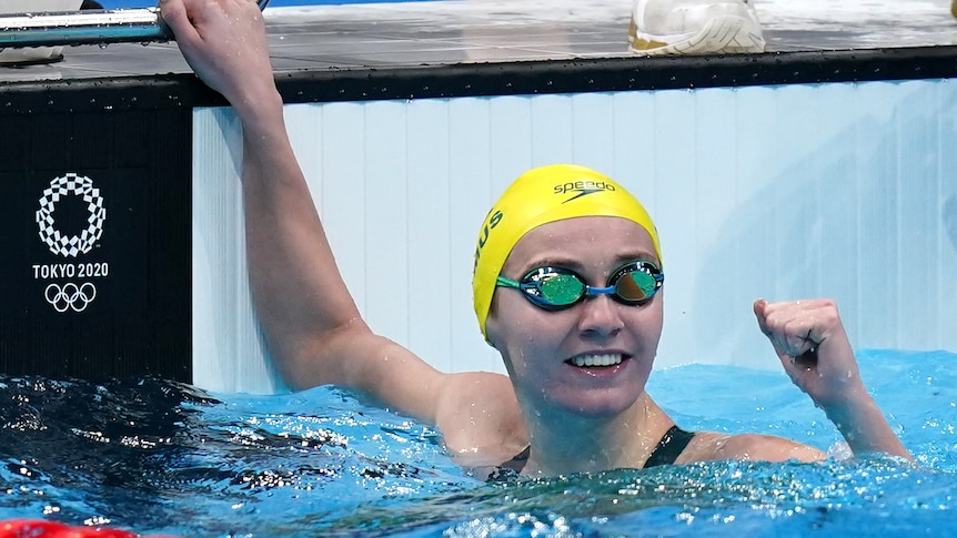 Ariarne Titmus, still wearing goggles in the pool, looks up and pumps her fist