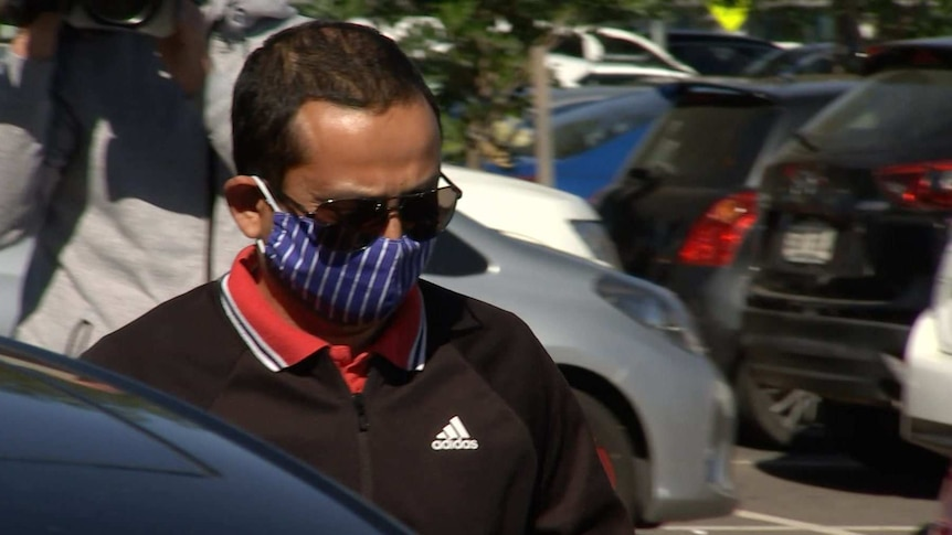A man wearing big sunglasses and a blue and white face mask walks toward a car in a busy carpark