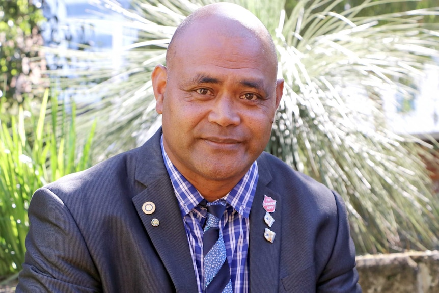 A head and shoulder shot of Moe Turaga in a suit, with shrubs in the background.