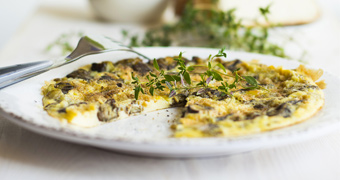 Close up of an omelette or frittata with fresh herbs on a white plate and table setting.