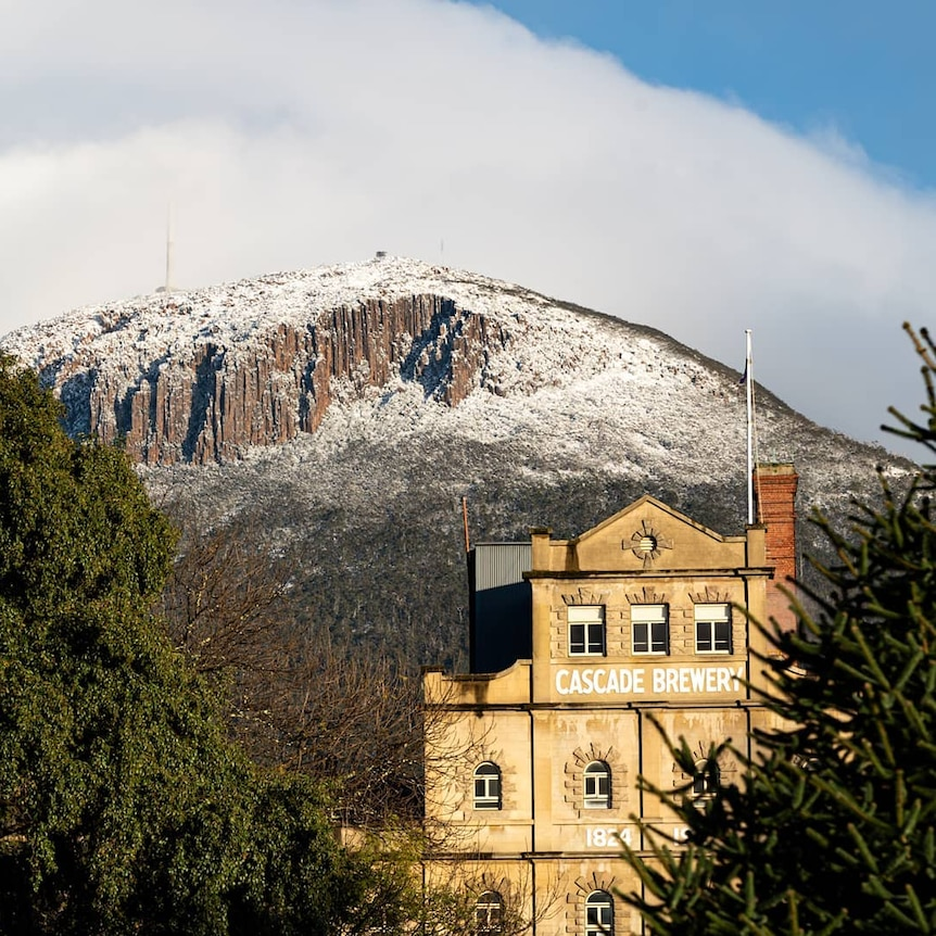 Mt Wellington covered in snow, with the Cascade Brewery in the foreground.