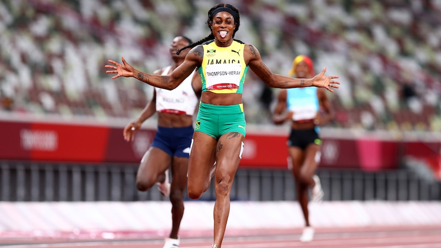 A Jamaican female sprinter sticks her tongue out after winning the 200m final at the Tokyo Olympics.