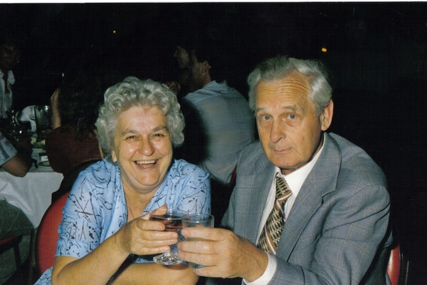 An old film photograph of Hen and Rose Nieman at a round dinner table at a function, with drinks in their hands.