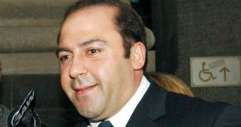 Tony Mokbel exiting a court surrounded by reporters.