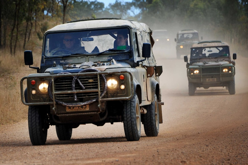 Australian Army Landrover 110s travel in convoy down a dirt road.