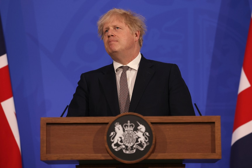 Boris Johnson pulls a serious face while speaking at a lectern