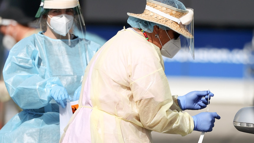 A woman wearing a face shield and mask and gloves looks down at a COVID swab test in her hand.