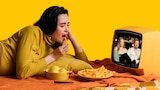 A woman eats chips while watching Married at First Sight on a small TV.