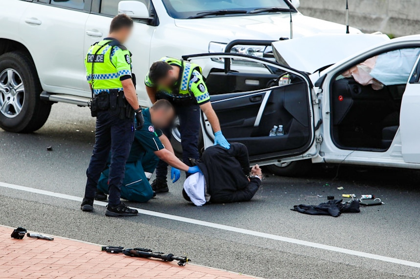 A paramedic speaks to a man on the ground in front of a crashed car.